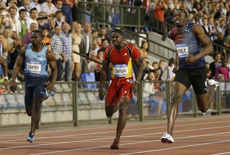 Usain Bolt of Jamaica (R) runs next to Nesta Carter of Jamaica (L) and Justin Gatlin of the U.S. on his way to win the men's 100 metres duri