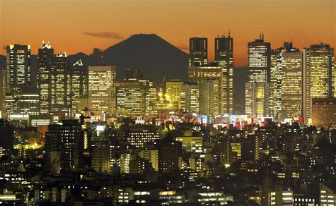 Skyscrapers in Tokyo's Shinjuku district frame Mount Fuji at dusk in this December 11, 2002 file photo. REUTERS/Kimimasa Mayama/Files