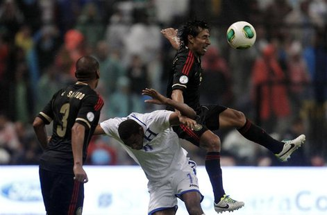 Mexico's Fernando Arce (R) jumps for the ball against Honduras' Jerry Bengston as Mexico's Carlos Salcido looks on during their 2014 World C