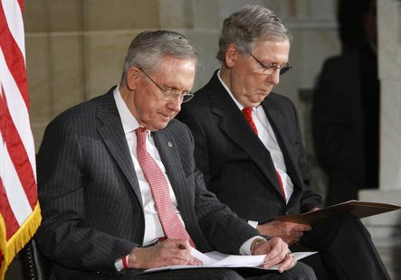 U.S. Senate Majority Leader Harry Reid (D-NV) (L) and Senate Minority Leader Mitch McConnell (R-KY) (R) look at their notes during a ceremon