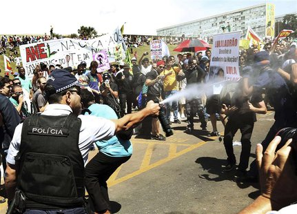 A policeman sprays anti-government demonstrators with tear gas outside the Congress in Brasilia, September 7, 2013. REUTERS/Gregg Newton