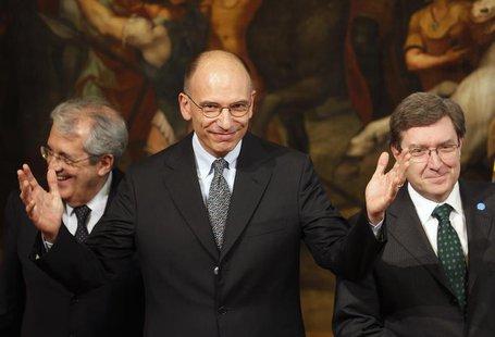 Italy's Prime Minister Enrico Letta (C) gestures next to Economy Minister Fabrizio Saccomanni (L) and Labour Minister Enrico Giovannini duri