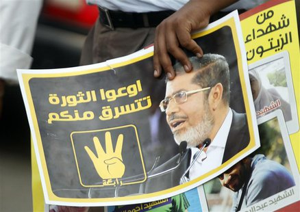 "A member of the Muslim Brotherhood and supporter of ousted Egyptian President Mursi holds a poster during a protest named ""People Protect th"