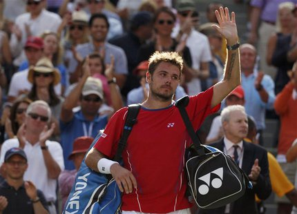 Stanislas Wawrinka of Switzerland waves as he departs the court after being defeated by Novak Djokovic of Serbia in their men's semi-final m
