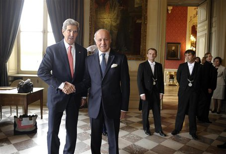 U.S. Secretary of State John Kerry (L) arrives for a meeting with French Foreign Affairs Minister Laurent Fabius (2nd L) at the Ministry of