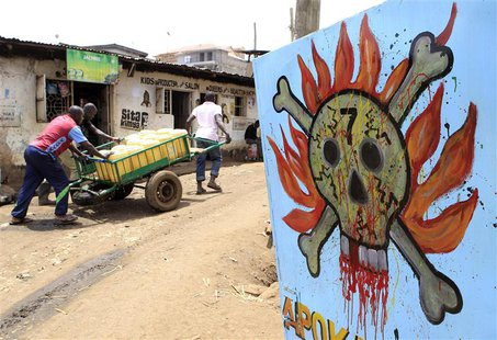 Men push their handcart past a danger sign at the sprawling Kibera slums in Nairobi September 6, 2013. REUTERS/Noor Khamis