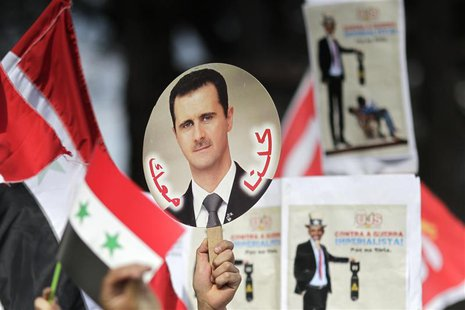 A student holds a sign with a picture of Syria's President Bashar al-Assad during a protest by a students' national union against possible U