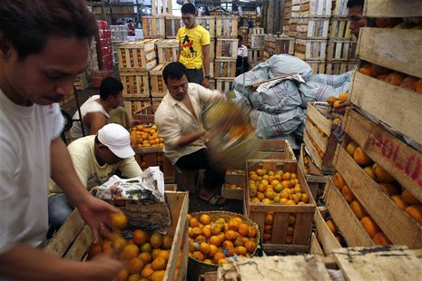 Workers sort out oranges at the Kramat Jati vegetable and fruit market in Jakarta September 6, 2013. REUTERS/Beawiharta