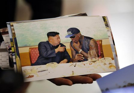 Former basketball star Dennis Rodman of the U.S. shows a picture which he took with North Korean leader Kim Jong-un as he arrives at Beijing