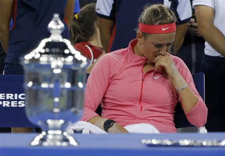 Victoria Azarenka of Belarus wipes her face as she sits by the winner's trophy (L) after being defeated by Serena Williams of the U.S. in th
