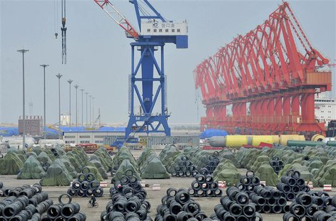 A worker rides his bicycle past piles of steel coils for export at a port in Yingkou, Liaoning province in this August 9, 2013 file photo. R