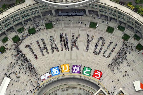 "An aerial view shows people sitting in formation to the words ""thank you"" and displaying signs that collectively read ""Arigato"" (Thank You)"