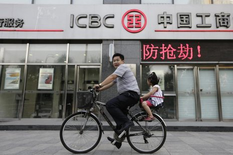 A man cycles a bike carrying his daughter past a branch of Industrial and Commercial Bank of China Ltd (ICBC) in Beijing, June 26, 2013. REU