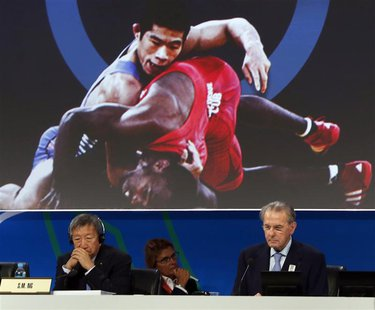 President of the International Olympic Committee (IOC) Jacques Rogge (R) listens to the presentation of wrestling to be included as an Olymp