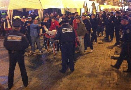 A photo, taken with a mobile phone, shows an injured English soccer fan lying on a stretcher and surrounded by medical personnel, police and