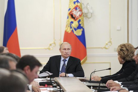 Russian President Vladimir Putin (C) chairs a meeting with members of the Security Council at the Novo-Ogaryovo residence outside Moscow, Se