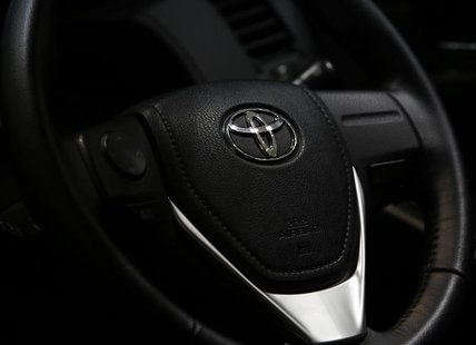 The logo of Toyota Motor Corp. is seen on a steering wheel of the company's car at the Toyota Motor's showroom in Tokyo August 1, 2013. REUT