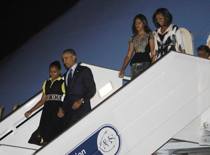 U.S. President Barack Obama (2nd L) and first lady Michelle Obama (R ) arrive with their daughters Sasha (L) and Malia in Dakar, June 26, 20