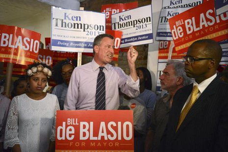 New York mayoral candidate Bill de Blasio, standing between his daughter Chiara (L) and district attorney candidate Ken Thompson (R), speaks