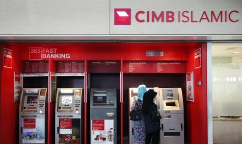 People withdraw cash from an automatic teller machine at a CIMB Islamic branch in Sepang outside Kuala Lumpur August 26, 2013. REUTERS/Bazuk