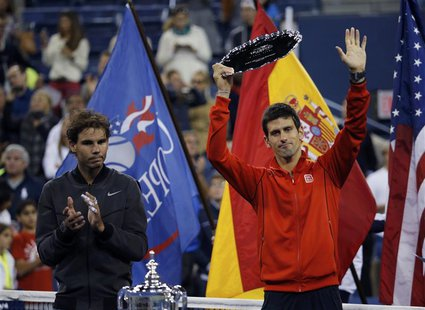 Rafael Nadal of Spain applauds as Novak Djokovic of Serbia raises his runner up trophy after Nadal won their men's final match at the U.S. O