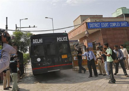 A police vehicle carrying four men accused of the gang rape of a 23-year-old woman on a bus on December 16, enters a court in New Delhi Sept