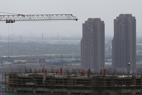 Construction workers are seen on a building in Shanghai September 4, 2013. REUTERS/Aly Song