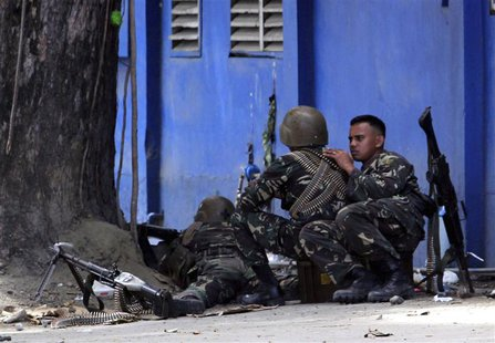 An army sniper aims his rifle at Moro National Liberation Front snipers from behind a tree in Zamboanga, where security forces are battling