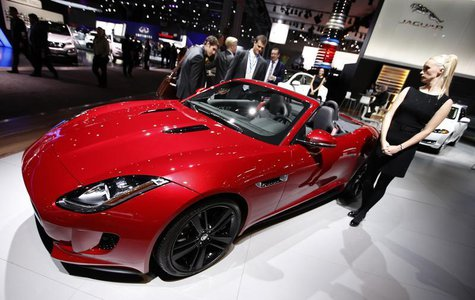 A model stands next to a Jaguar F Type S convertible model, winner of the 2013 World Car Awards World Car Design of the Year during a press