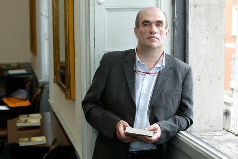 Irish author Colm Toibin poses for photographers after he won the world's richest literary prize for a single work of fiction in English on