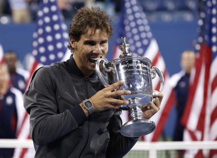 Rafael Nadal of Spain bites his trophy after defeating Novak Djokovic of Serbia in their men's final match at the U.S. Open tennis champions