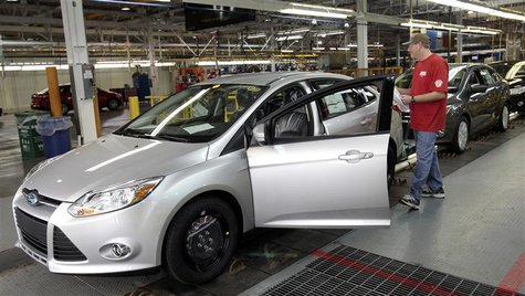 A Ford Motor assembly worker inspects the new 2012 Ford Focus vehicles on the final production line at Michigan Assembly Plant in Wayne, Mic