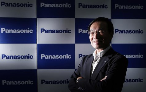 Panasonic Corp's President Kazuhiro Tsuga poses in front of company logos after an interview with Reuters in Tokyo September 4, 2013. REUTER