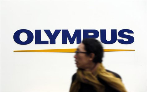 A man passes a logo of Olympus Corp outside the company's showroom in Tokyo December 21, 2012. Olympus and Sony Corp said on Friday that a p