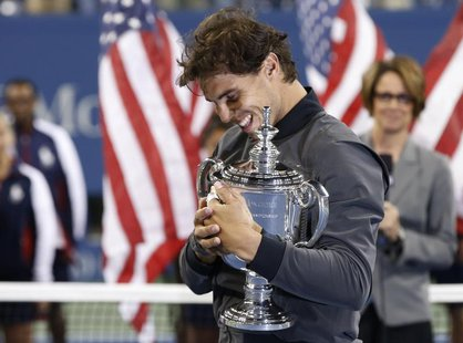 Rafael Nadal of Spain embraces his trophy after defeating Novak Djokovic of Serbia in their men's final match at the U.S. Open tennis champi