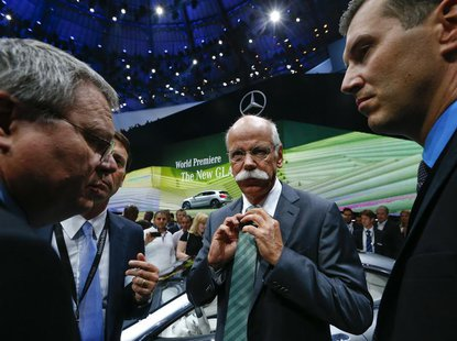 Daimler Chief Executive Dieter Zetsche (C) adjusts his tie during the presentation of the new SUV Mercedes GLA on a media preview day at the