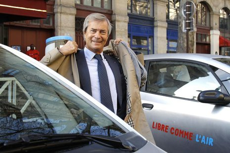 Vincent Bollore, CEO of investment group Bollore, stands by Autolib' electric cars during the inauguration of the the Autolib' service in Pa