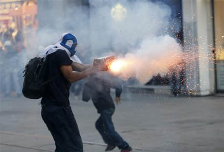 A masked demonstrator uses fireworks against riot police with a home made device during a protest in central Istanbul September 10, 2013. RE