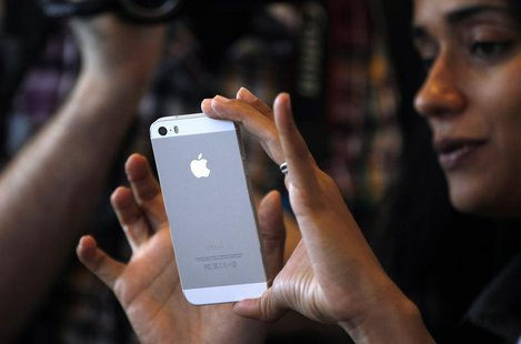 A woman tries the silver colored version of the new iPhone 5S after Apple Inc's media event in Cupertino, California September 10, 2013. REU