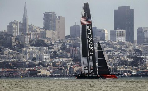Oracle Team USA sails against the city skyline against Emirates Team New Zealand during Race 3 of the 34th America's Cup yacht sailing race