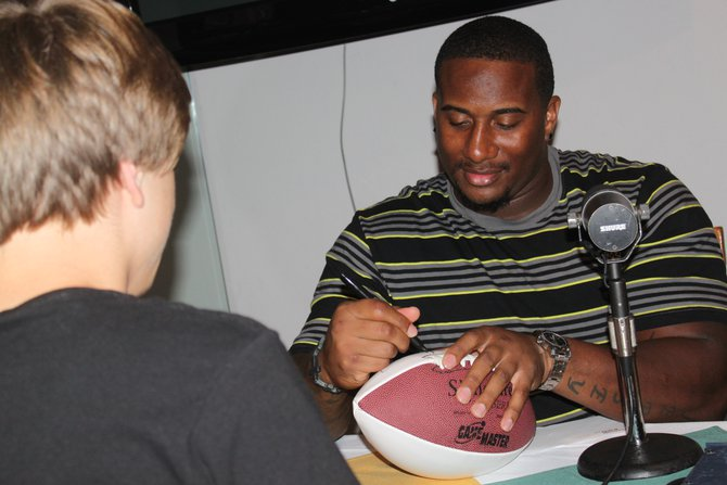 #76 Mike Daniels signs autographs during breaks on the 5th Quarter Show