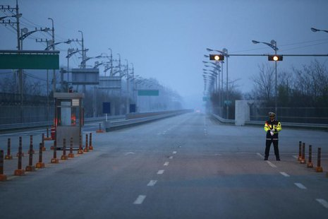 A South Korean police officer stands guard on an empty road connecting the Kaesong Industrial Complex (KIC) inside the North Korean border w