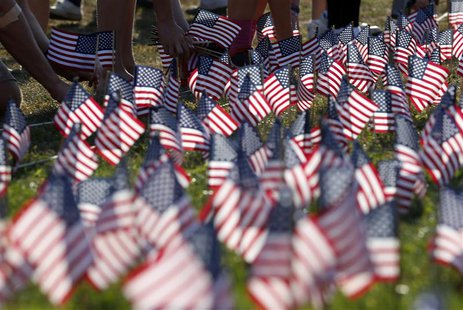 People plant some of the 3000 U.S. flags placed in memory of the lives lost in the September 11, 2001 attacks, at a park in Winnetka, Illino