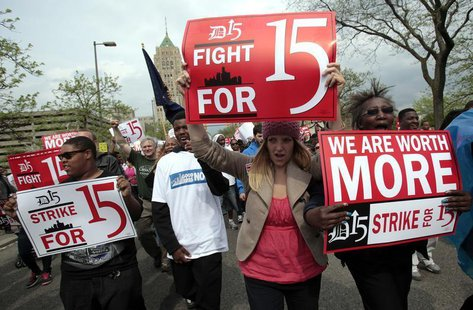 A group of workers and labor activists march down West Grand Boulevard as they demand a raise in the minimum wage for fast food workers in D