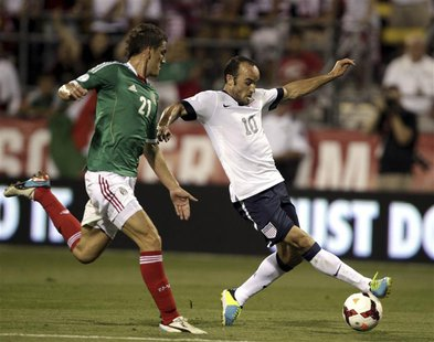 United States' Landon Donovan (10) fights for the ball with Mexico's Hiram Mier (21) during the first half of their 2014 World Cup qualifyin