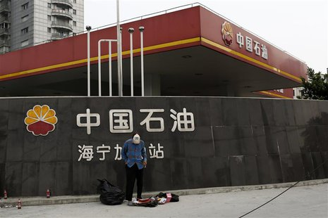 A garbage collector stands in front of a PetroChina company logo at its gas station in Shanghai September 9, 2013. REUTERS/Aly Song