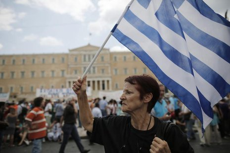 An anti-austerity protester holds a Greek flag during a rally in Athens July, 16, 2013. REUTERS/John Kolesidis