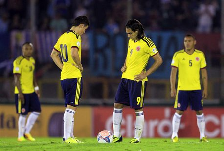 Colombia's players restart the game after conceding a goal to Uruguay's during their 2014 World Cup qualifying soccer match in Montevideo, S