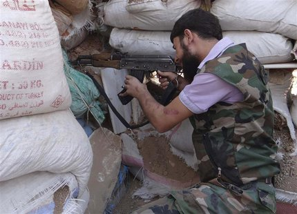 A Free Syrian Army fighter aims his weapon behind sandbags in the eastern al-Ghouta, near Damascus, September 9, 2013. Picture taken Septemb