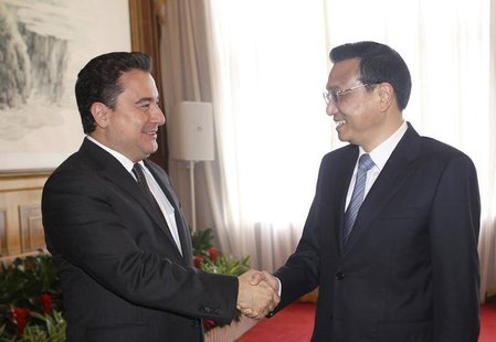 China's Premier Li Keqiang shakes hands with Turkey's Deputy Prime Minister Ali Babacan (L) during the Annual Meeting of the New Champions,